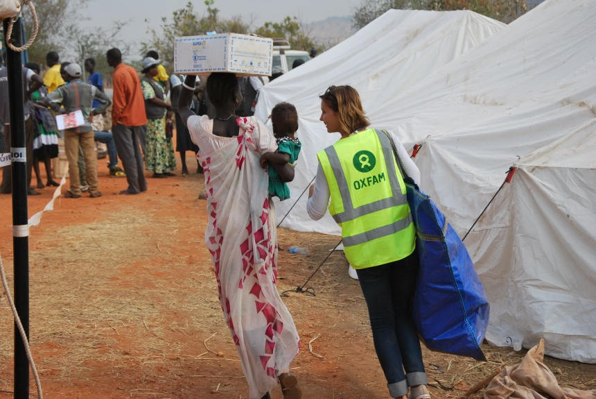 An_Oxfam_member_of_staff_helps_to_carry_one_family's_newly_received_non-food_items_home_in_UN_House,_Juba_(12046957855)